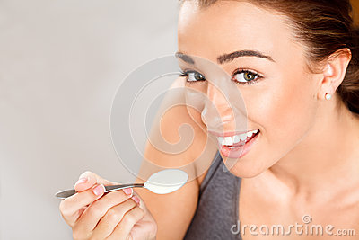 Attractive young woman eating yogurt