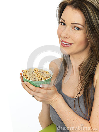 Free Attractive Young Woman Holding A Bowl Of Salted Peanuts Stock Images - 58627704