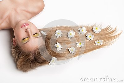 Attractive young woman lying covered with flowers