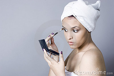 Attractive young woman putting on makeup