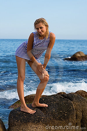 Attractive young woman on a rocky seashore