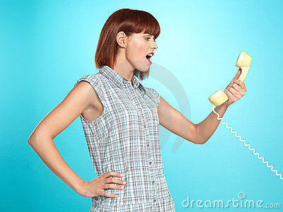 Attractive young woman screaming on the telephone
