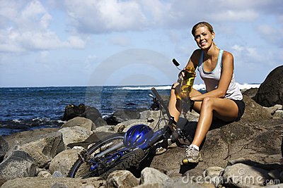 Attractive Young Woman Sitting With Bicycle on Roc