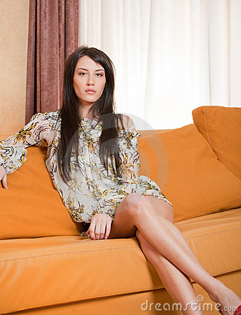 Attractive young woman sitting on sofa