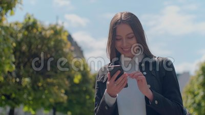Attractive young woman at the sunny city streets and chatting with friends, joyful hipster girl using cellphone outdoors. Sunset background stock video footage