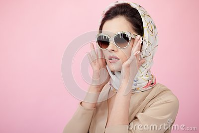 Attractive young woman wearing in silk scarf, touches his sunglasses with his hands, isolated on pink background. Stock Photo