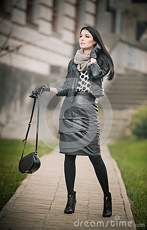 Attractive young woman in a winter fashion shot. Beautiful fashionable young girl in black leather waking on avenue. Elegant woman