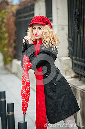 Attractive young woman in a winter fashion shot. Beautiful young girl with red umbrella in the street