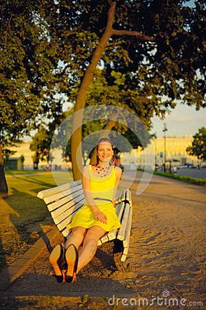 Attractive young woman in yellow dress, sitting in a summer park on a bench