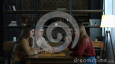 Young men teaching chess game to joyful girlfriends stock video footage