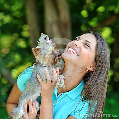Attractive younggirl playing with her puppy outdoor