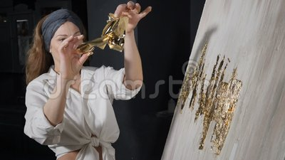 Attraente artista femminile che applica la foglia d'oro alla sua opera d'arte L'artista addobba l'immagine con un piccolo foglio  video d archivio