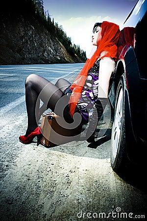 Attraktiv bilflicka nära resväska