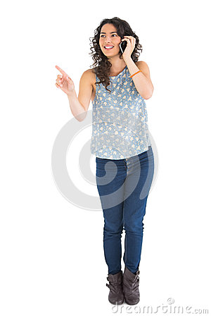 Attraktiv brunett som pekar på något, medan ha påringning