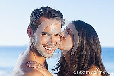 Attraktiv kvinna som kysser hennes pojkvän på kinden