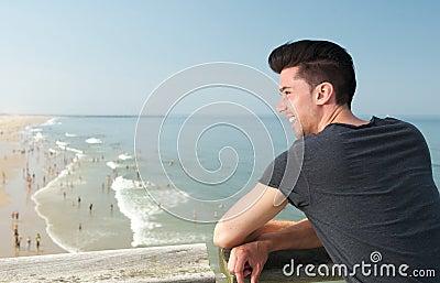 Attraktiv ung man som ler på stranden