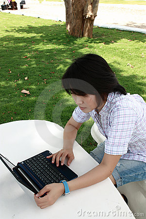 Attraktive asiatische Frau ist draußen mit Laptop