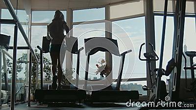 Attraktive Frau, die auf Tretmühle in der Sportturnhalle läuft
