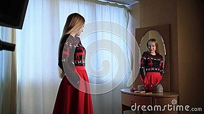 Attraktive Frau, die elegante Ausstattung im Spiegel überprüft stock video footage