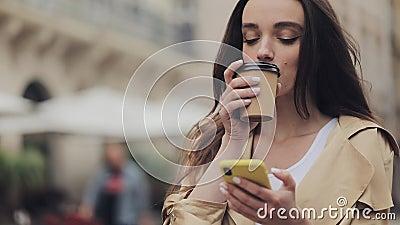 Attraktive junge Mädchen, die auf ihrem Smartphone tippen und lächelnd ein Papier Cup trinken Cofee in der Altstadt stock video footage
