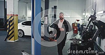Attraktive Mechanik mit guter Laune in einem gleichmäßigen Tanz lustig vor der Kamera bei der Arbeit über einem Auto stock video footage