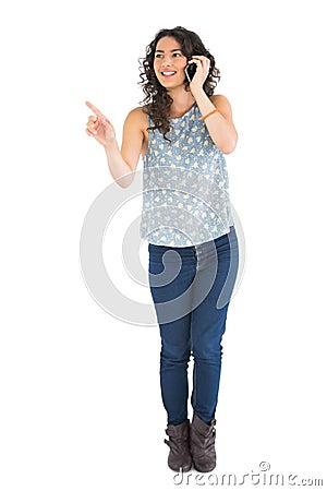 Attraktiver Brunette, der auf etwas beim Haben des Telefonanrufs zeigt