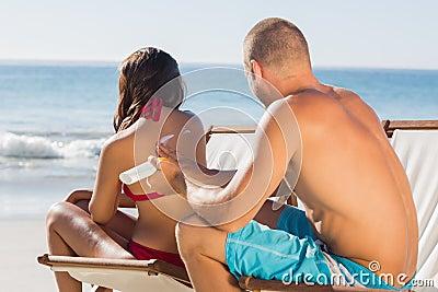 Attraktiver Mann, der zurück Sonnencreme auf seinen Freundinnen aufträgt