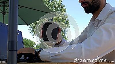 Attraktiver Typ mit einem Bart in einem weißen Hemd sitzt an einem Tisch in einem Straßencafé, tippt auf eine Laptop-Tastatur und stock footage