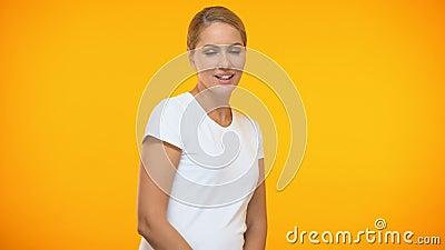 Attraktives Frauentanzen auf dem orange Hintergrund, der Kamera, Flirt, Weiblichkeit blinzelt stock video