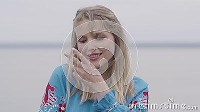 Attraktives junges blondes Mädchen im schönen blauen langen Sommerkleid mit der Stickerei, die ihr Haar berührt Konzept der Mode stock video footage