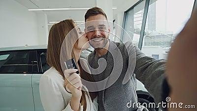 Attraktives junges Paar nimmt selfie mit Autoschlüsseln im modernen Bewegungsausstellungsraum, nachdem es neues Automobil gekauft stock video