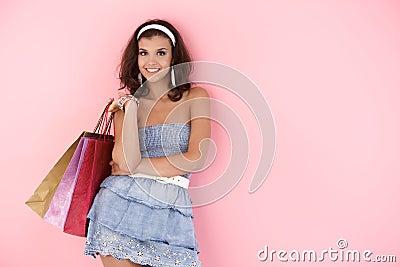 Attraktives Mädchen mit Einkaufenbeuteln am Sommer