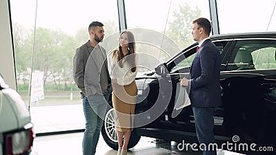 Attraktives Paar spricht mit AutoVerkaufsleiter im Luxusauto-vertragshändler und betrachtet schönes schwarzes Automobil stock video footage