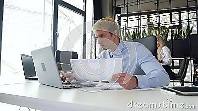 Attraktives Portrait von gut aussehenden jungen blonden Geschäftsleuten, die einen Bericht mit Tabellen mit Daten auf Laptop bei  stock footage