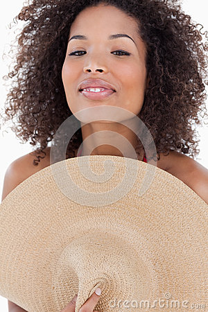 Attraktivt kvinnanederlag henne huvuddel bak en hatt