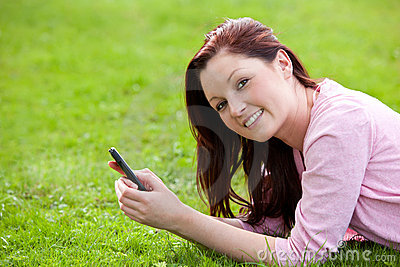 Attrative young pregnant woman texting in a park