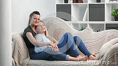 Attrayant couple de femmes homosexuelles se posant allongé sur un canapé et se reposant à l'intérieur de la maison banque de vidéos