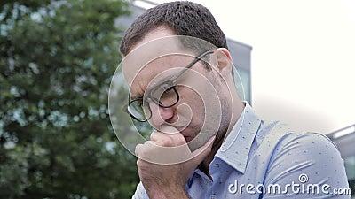 Attrayant homme aux cheveux bruns qui lit quelque chose sur un ordinateur portable banque de vidéos