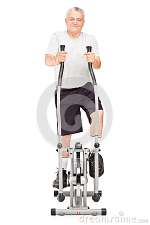 Мature man excersing on a cross trainer