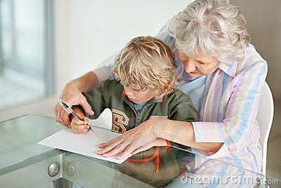 Ature woman helping her grandson to write on a paper