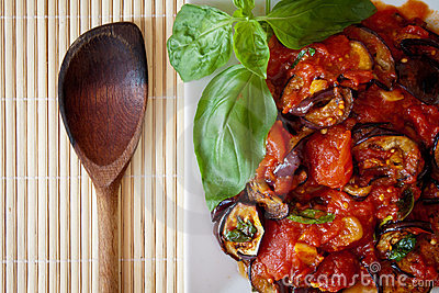 Aubergines in tomato sauce with wooden spoon