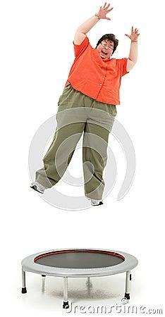 Aufgeregte beleibte Vierziger-Frau, die auf Trampoline springt