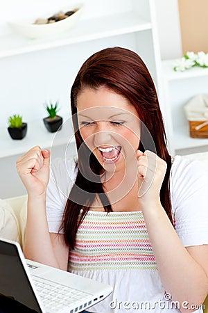 Aufgeregte Frau mit den Armen oben vor ihrem Laptop