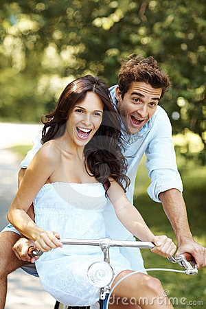Aufgeregte junge Liebespaare, die Fahrrad fahren
