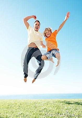 Aufgeregter Vater mit seinem kleinen Sohn, der in einer Luft springt