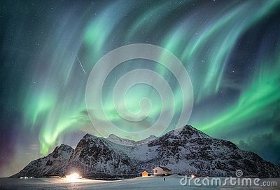 Aurora borealis with starry over snow mountain range with illumination house in Flakstad, Lofoten islands, Norway Stock Photo