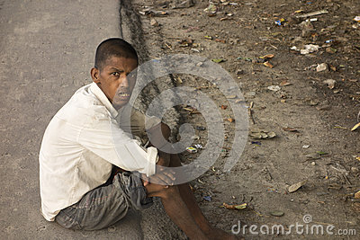 Autism profile hopeless poor boy sitting in road Editorial Image
