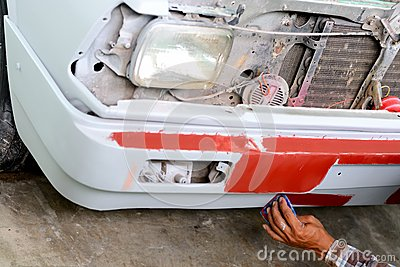 Auto mechanic preparing the front bumper of a car for painting