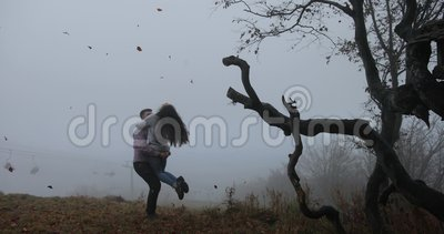 Automne foncé, paysage de montagne L'homme tourbillonne la femme avant des arbres avec les feuilles tombées couvertes de brouilla banque de vidéos
