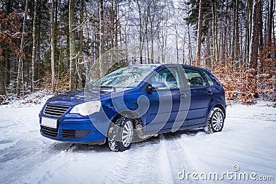 Automobile blu nel paesaggio della foresta di inverno